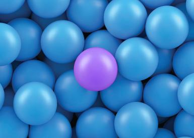 uma bola roxa no meio de várias bolas azuis